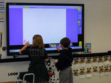 First Grade Students Work Together On an Interactive Board